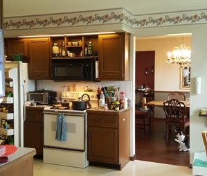 "the ""before"" kitchen had wallpapered soffits and tired cabinets"