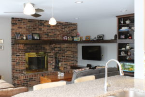 The family room has a fresher, lighter look with open shelves and bright ceiling.