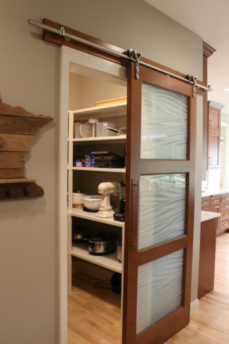 The walk-in pantry sports a patterned glass door that allows natural light but doesn't display all the kitchen staples.