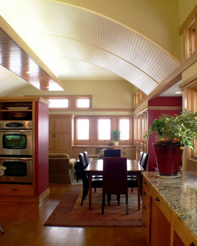 This great room is divided by curved ceiling treatments